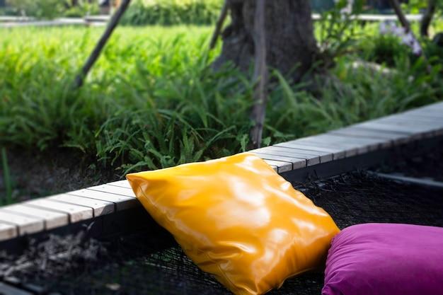 Cuscini colorati su rete seduta in mezzo alla natura