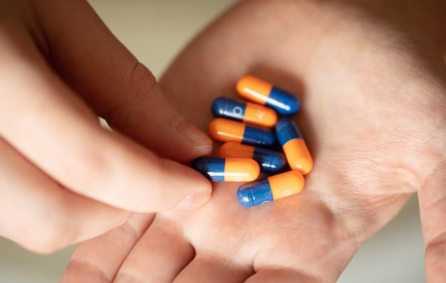 Pillole colorate e medicine in mano
