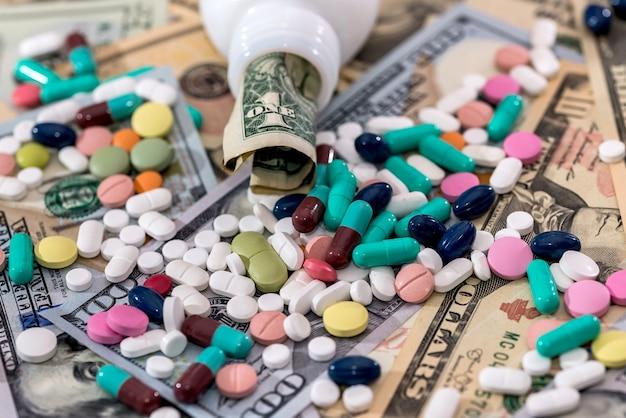 Pillole colorate con banconote in dollari da vicino