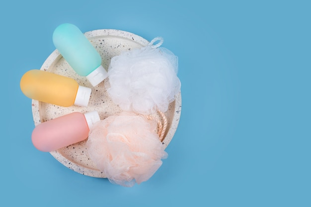 Contenitori di plastica colorati per shampoo, balsamo per capelli e gel doccia con salviette su un vassoio di marmo. prodotti cosmetici per spa e accessori da bagno su sfondo blu