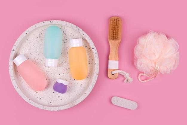 Contenitori di plastica colorati per shampoo, balsamo per capelli e gel doccia con salviette su un vassoio di marmo. prodotti cosmetici per spa e accessori da bagno su sfondo rosa