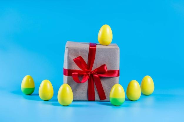 Uova di pasqua di plastica colorate e un regalo in carta artigianale su sfondo blu.