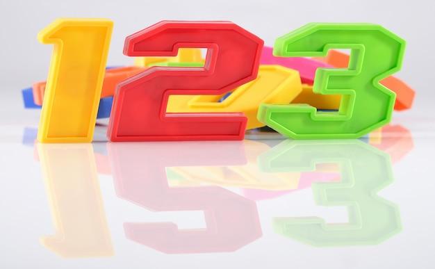Numeri di plastica colorati 123 con riflesso su sfondo bianco