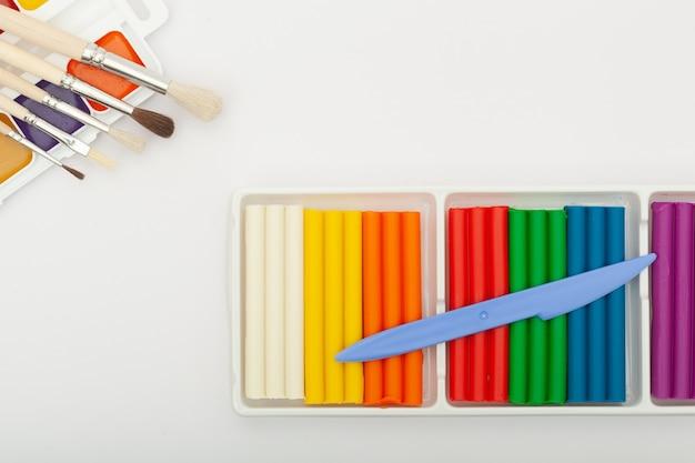Plastilina colorata e colori ad acquerello come set scolastico per il disegno. concetto di creatività