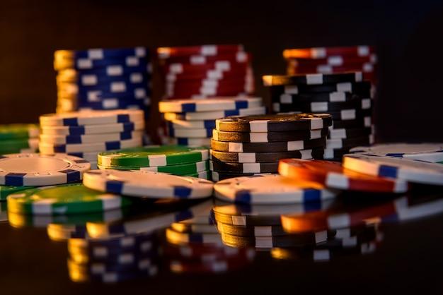 Fiches da poker colorate sulla superficie riflettente da vicino