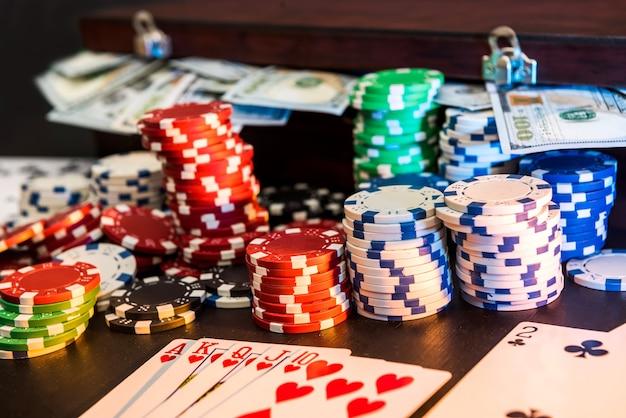 Fiches da poker colorate con carte da gioco e dollari americani su sfondo scuro.