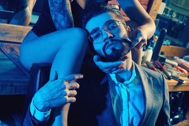 Ritratto colorato di bella coppia: uomo brutale in abito elegante e ragazza sexy con un tatuaggio che indossa lingerie nel negozio di barbiere