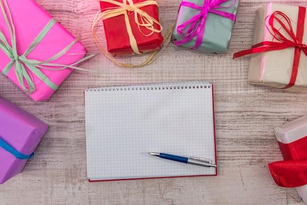 Scatole regalo colorate con blocco note aperto. la pianificazione del nuovo anno. nuovo inizio