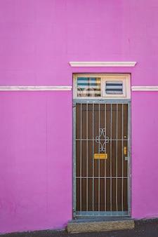 Facciata viola variopinta e vecchia porta della casa nell'area di bo kaap, cape town