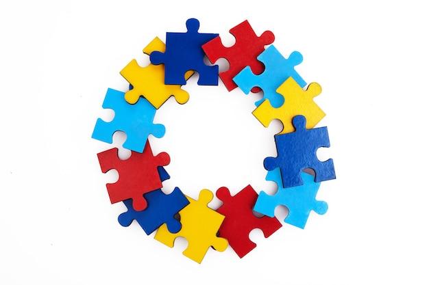 Puzzle colorati cornice rotonda su sfondo bianco, concetto di autismo della prima infanzia, copia spazio, spazio del testo.