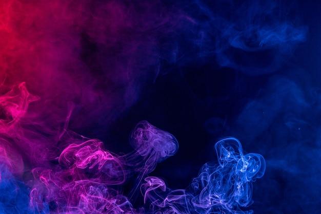 Fumo colorato di colore rosso e blu isolato su sfondo nero