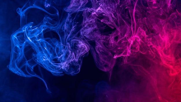 Fumo colorato di colore rosso e blu isolato su sfondo nero scuro