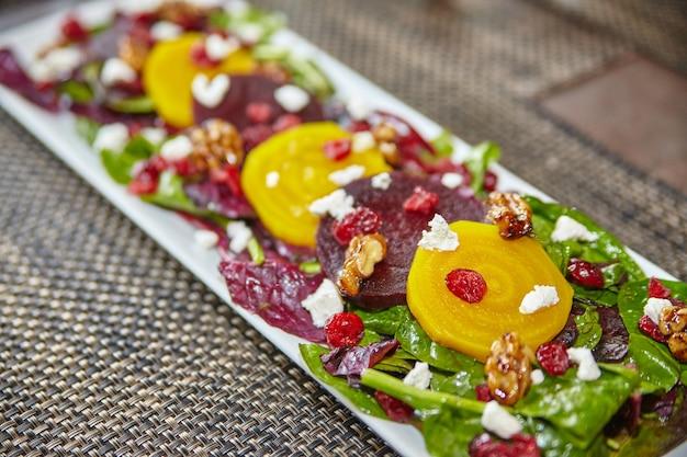 Insalata di barbabietola rossa e gialla colorata con formaggio feta bianco su un letto di verdure su un piatto lungo