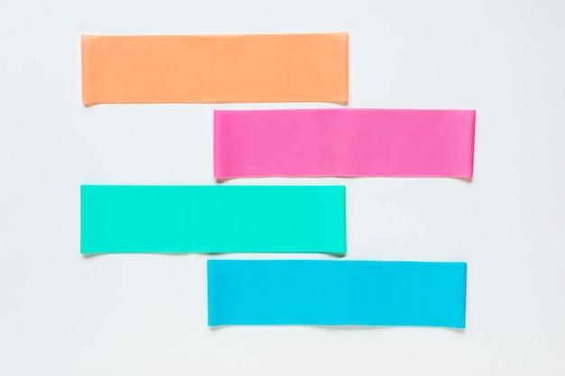 Colorate bande di fitness resistenza su sfondo bianco piatto laici accessori per lo sport