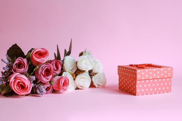 Rosa colorata con confezione regalo su sfondo rosa