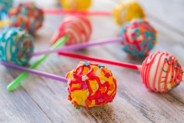 Dolci rotondi colorati. caramelle su fondo di legno. cake pop con ripieno di crema. piccola vacanza per i bambini.