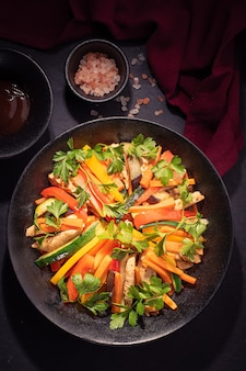 Insalata colorata con pollo fritto e una fetta di carota e zucchine su sfondo nero.