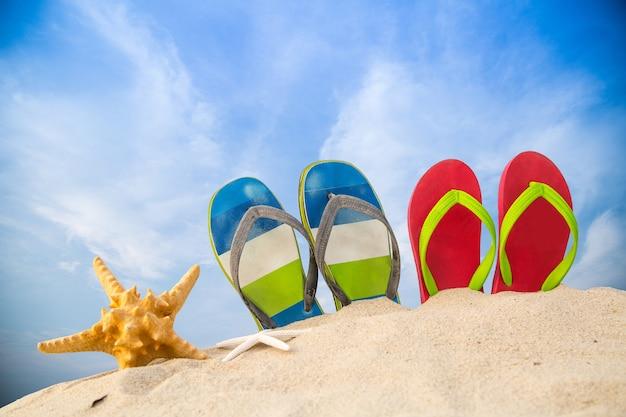 Sandali colorati sulla spiaggia con il concetto di estate.