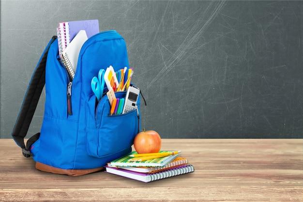Materiale scolastico colorato in zaino su fondo in legno
