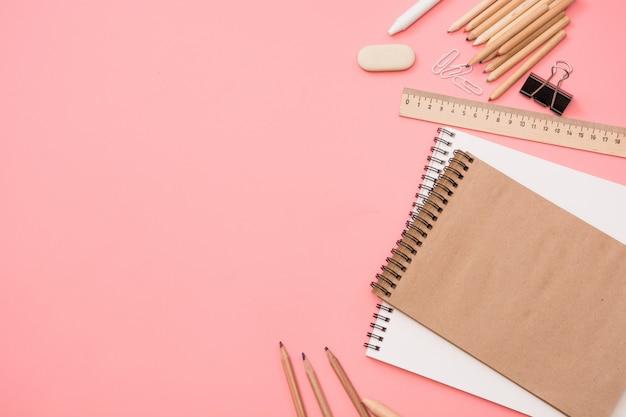 Materiale scolastico colorato su rosa pastello. vista dall'alto, piatto.