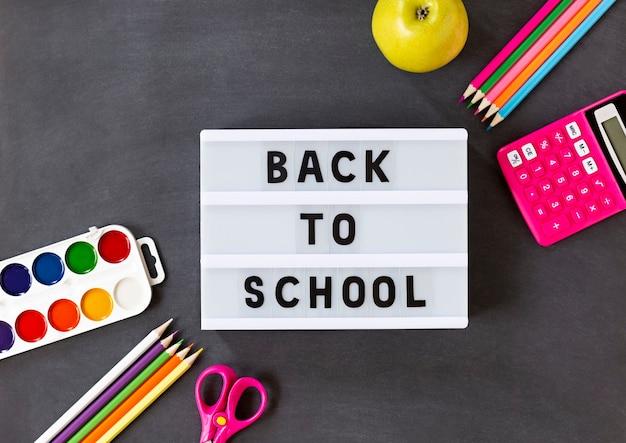 La scuola colorata fornisce materie su una lavagna nera con scatola luminosa e testo per tornare a scuola. piattamente.
