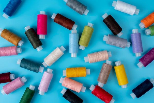 Filo per cucire colorato in studio su uno sfondo di colore blu. motivo di sfondo arcobaleno di filo