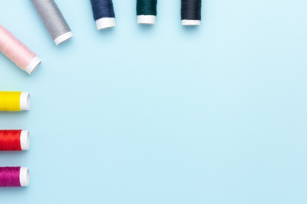 Filati cucirini variopinti su una priorità bassa blu.