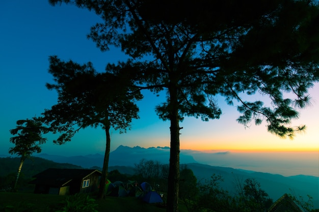 Cielo colorato al mattino sulle montagne nel nord della thailandia con tende e casa in cima al monte.