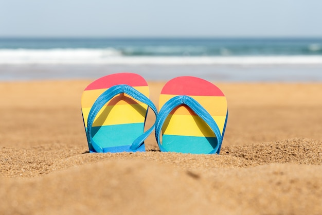 Pantofole colorate sulla spiaggia in una giornata estiva - bandiera del gay pride - infradito