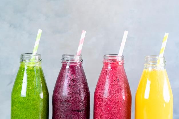 Frullato colorato in bottiglie di vetro frullati di frutta estiva in barattoli disintossicazione sana e concetto di cibo dietetico