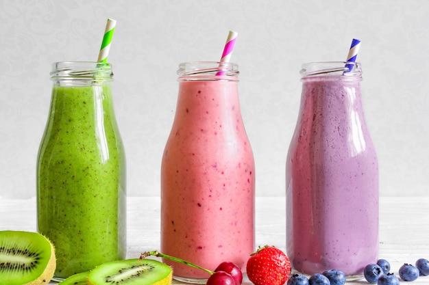 Frullati colorati in bottiglia: verde, viola e rosso con frutti e bacche