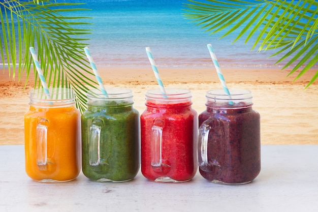 Bevande frullate colorate in barattoli di vetro sul tavolo bianco dalla spiaggia