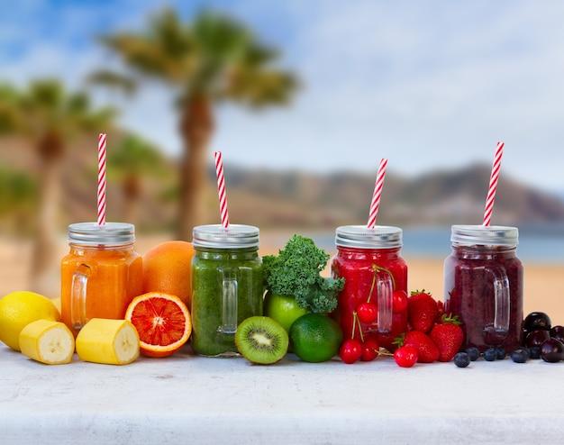 Bevande frullate colorate in barattoli di vetro sul tavolo bianco