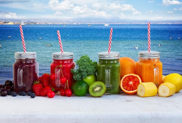 Bevande frullate colorate in barattoli di vetro con ingredienti in riva al mare