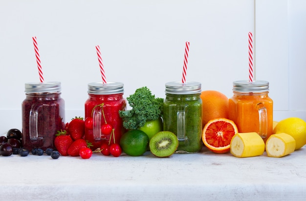 Bevande frullate colorate in barattoli di vetro con ingredienti