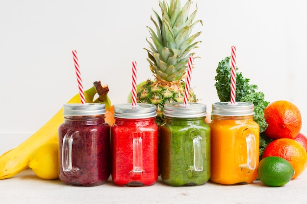 Bevande frullate colorate in barattoli di vetro con cannucce e ingredienti