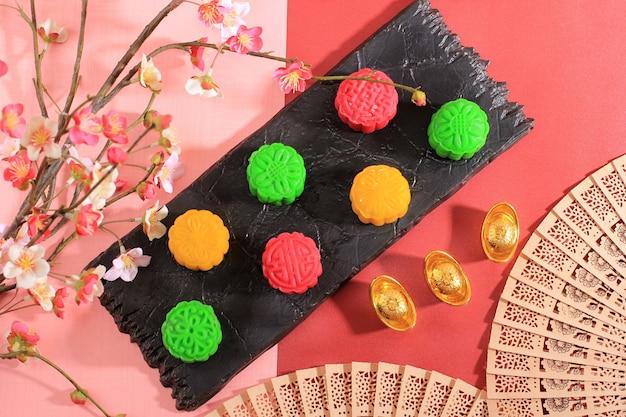 Torta di luna di pelle di neve colorata. nuova variante di mooncake, crema pasticcera ripiena di pasta mochi, pasta di fagioli rossi o fagioli verdi. modellato in stampo mooncake.