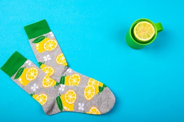 Calzini colorati e tazza di tè alle erbe con agrumi limone isolato su superficie blu, vista dall'alto