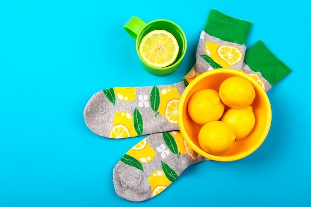 Calzini colorati e tazza di tisana con limone e ciotola gialla con limoni