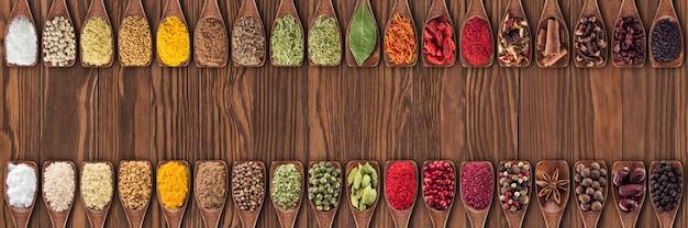 Spezie colorate ed erbe aromatiche come elemento di design dell'imballaggio alimentare. raccolta di condimenti in cucchiai di legno sul fondo della tavola.