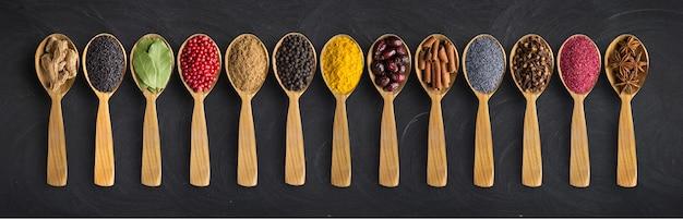 Spezie colorate sul tavolo. condimenti ed erbe aromatiche in cucchiai di legno. sapori come sfondo per l'imballaggio con il cibo.