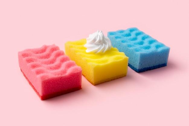 Spugne colorate per lavare i piatti con schiuma su sfondo rosa. concetto di servizio di pulizia