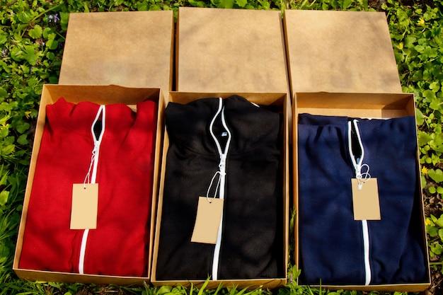 Abiti sportivi colorati con etichette piegate in scatole di cartone giacciono a terra con erba.