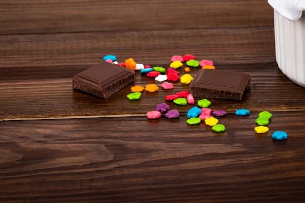 Spruzzi colorati e pezzi di cioccolato su sfondo di legno con spazio di copia.