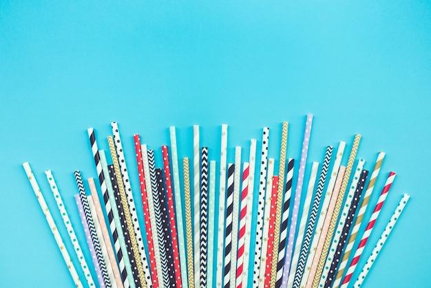 Collezioni di cannucce colorate su sfondo pastello