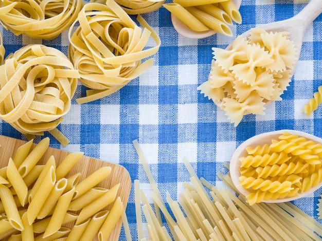 Composizione colorata e stilista. concetto di cucina e cibi italiani. selezione di pasta secca mista su asciugamano di lino bianco e blu come sfondo. vista dall'alto piatta con copyspace per testo, logo o altro.