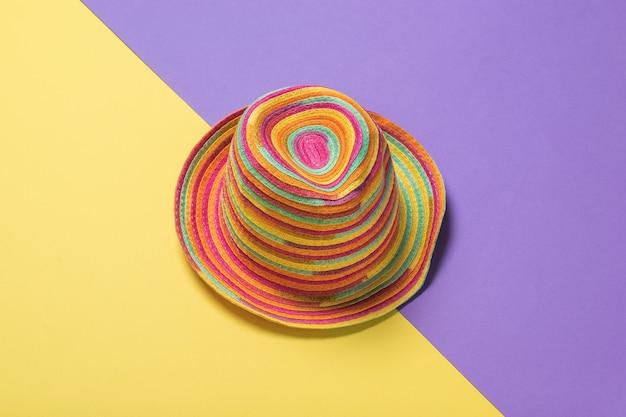 Cappello estivo colorato su una superficie lilla e gialla