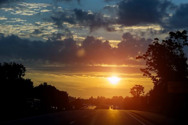 Scena colorata dell'alba al traffico sull'autostrada con messa a fuoco morbida delle auto