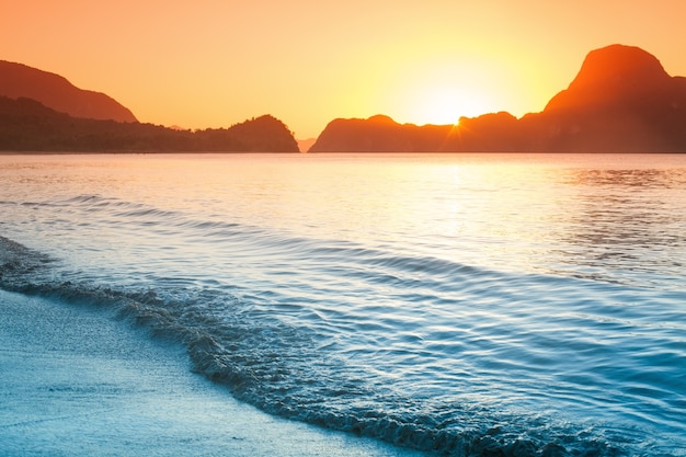 Tramonto colorato sulla spiaggia con rocce nelle filippine