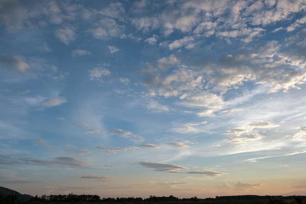Tramonto variopinto e alba con nuvole. colore blu e arancione della natura. molte nuvole bianche nel cielo blu. il tempo è sereno oggi. tramonto tra le nuvole. il cielo è crepuscolare.